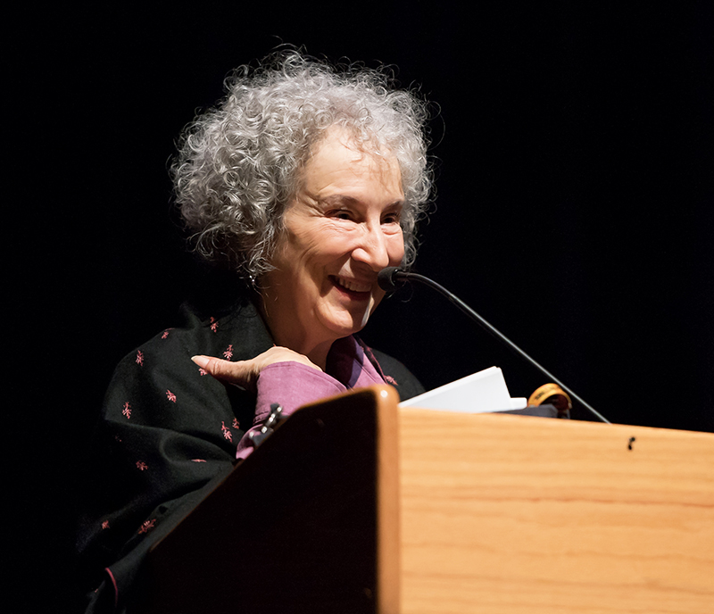 Margaret Atwood standing behind a microphone